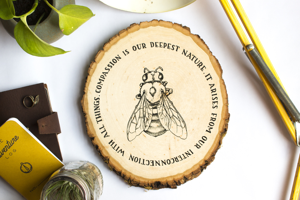 """compassion"" bee design screen printed on wood plaque"