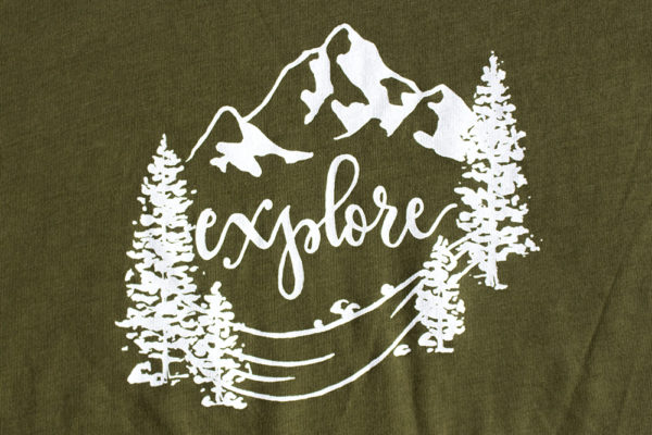 "Explore tee design closeup. Trees mountains and river with hand lettered ""explore"""